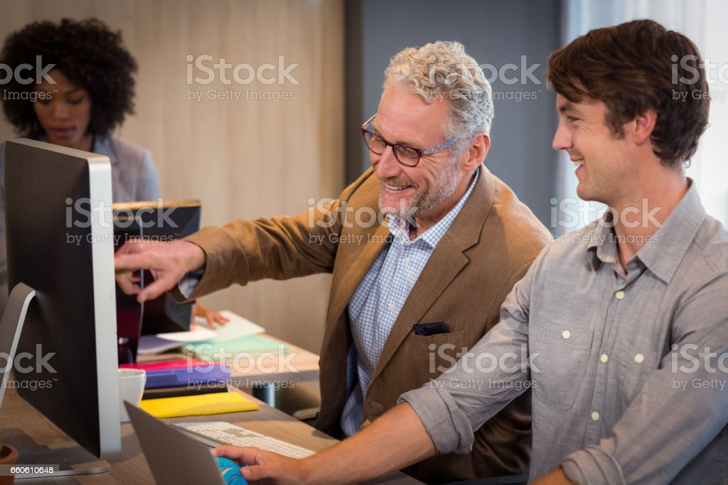 Businessman explaining colleagues over computer royalty-free stock photo