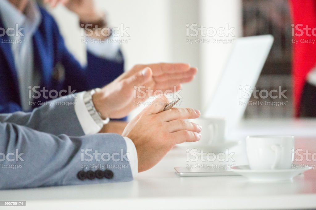 Businessman explaining his views during meeting Close up of businessman sitting at table and explaining his ideas to colleagues during meeting. Focus on businessman hands gesturing while sharing ideas. Adult Stock Photo