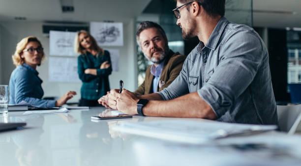 businessman explaining new business ideas to peers - persona in secondo piano foto e immagini stock