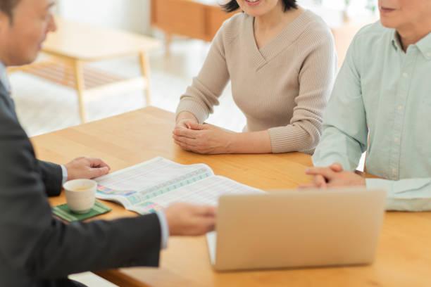 中年夫婦に説明するビジネスマン - 助言 ストックフォトと画像