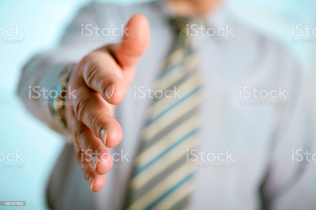 A businessman extending his hand into a handshake royalty-free stock photo