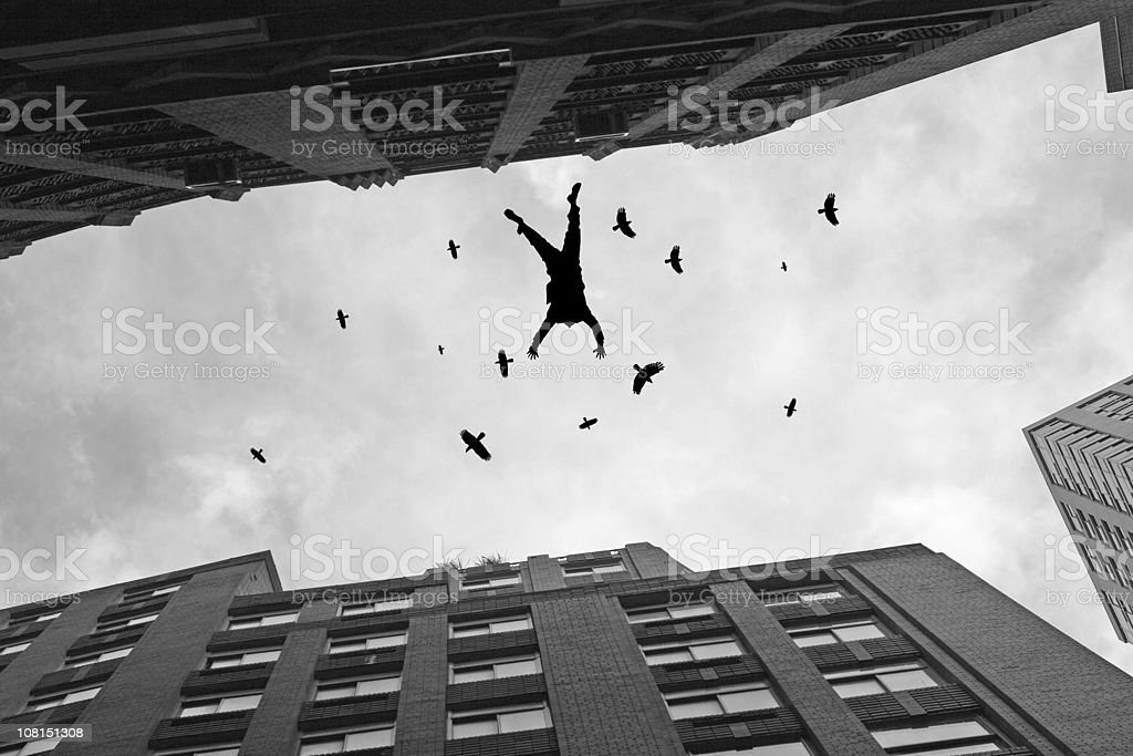 Businessman Falling Off Office Building Roof with Birds Flying stock photo