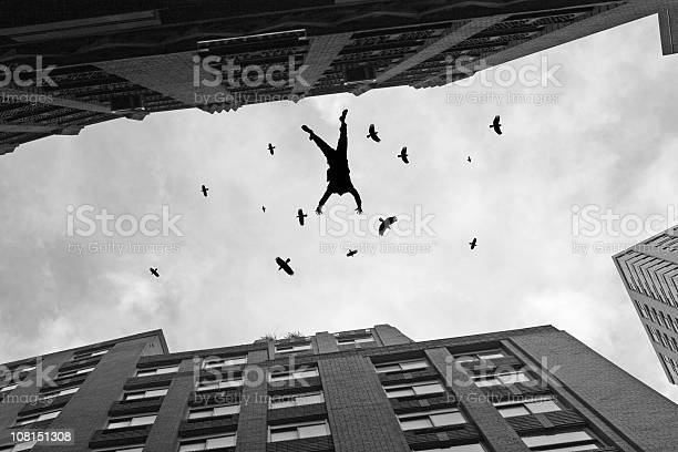 Photo of Businessman Falling Off Office Building Roof with Birds Flying