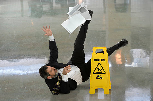 Businessman Falling on Wet Floor Senior businessman falling on wet floor in front of caution sign falling stock pictures, royalty-free photos & images