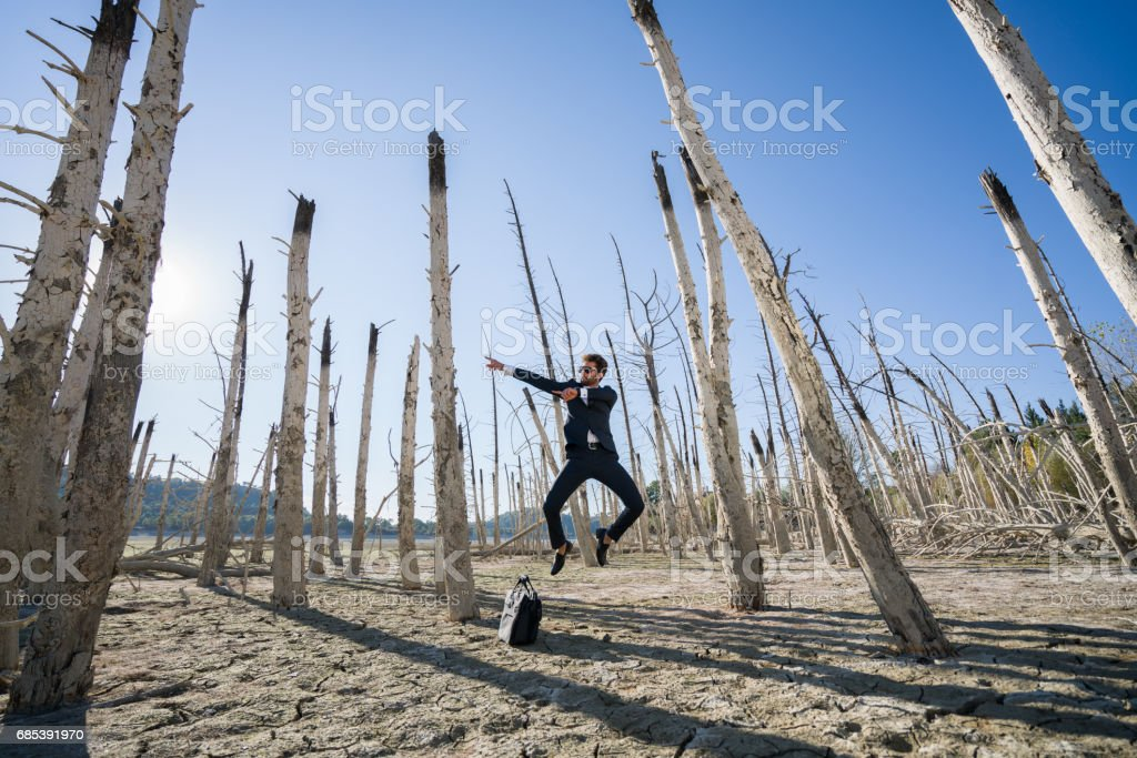 Businessman ,fashion model jumping on cracked earth royalty-free stock photo