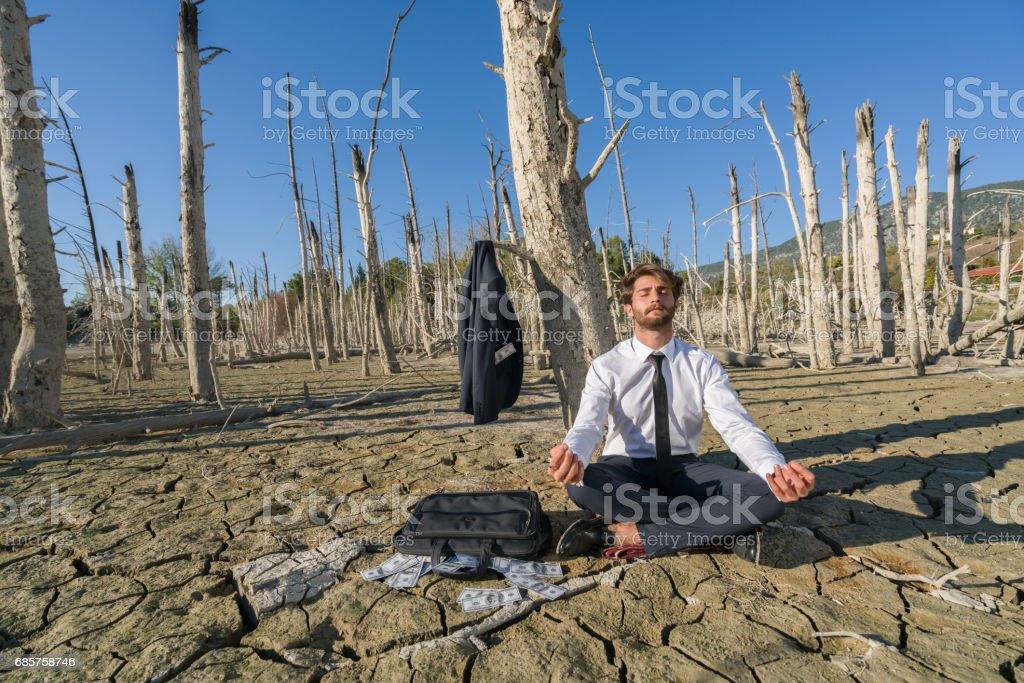 Zakenman, fotomodel rustend op gebarsten aarde royalty free stockfoto