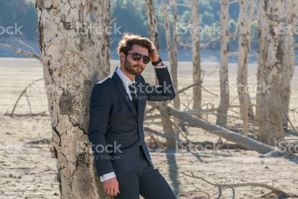 Businessman ,fashion model standing on cracked earth foto de stock royalty-free