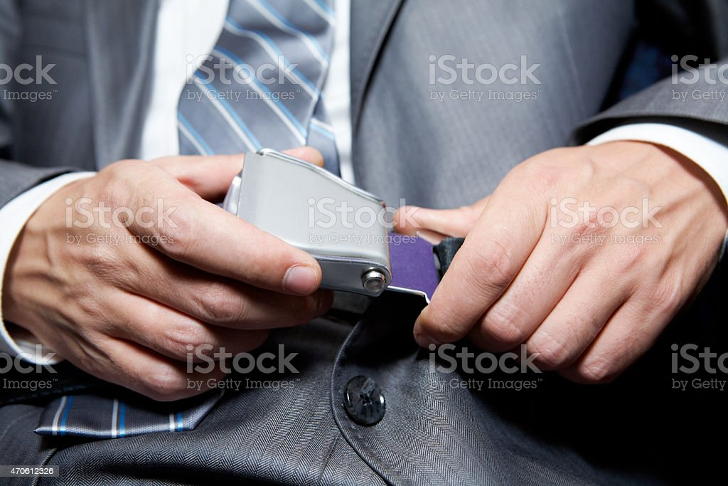 Businessman fastening his seatbelt for safety stock photo