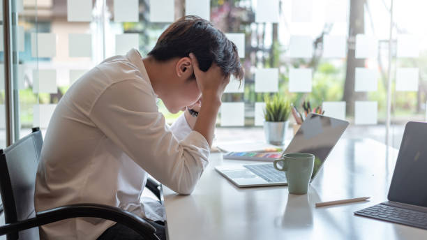 Businessman feel tired from long hours working on laptop in the office. Businessman feel tired from long hours working on laptop in the office. stress asian stock pictures, royalty-free photos & images