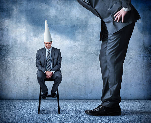 Businessman Feeling Like A Dunce A businessman sits on a stool wearing a dunce cap as a much larger over sized man stands and looks over him.  The businessman wearing the dunce cap looks like he's feeling very bad about himself. low self esteem stock pictures, royalty-free photos & images