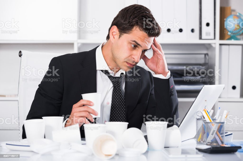 Businessman feeling thirsty in hot office stock photo