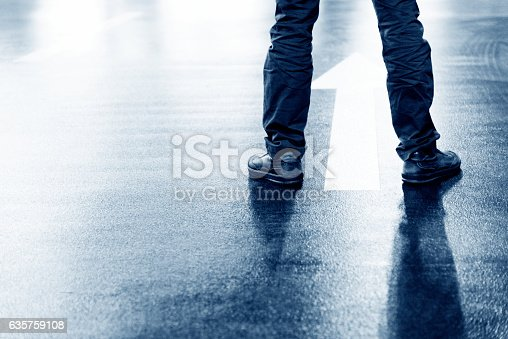 istock Businessman feet and direction arrow on floor 635759108