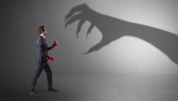 Businessman fighting with scary hand shadow picture id1182939027?b=1&k=6&m=1182939027&s=612x612&w=0&h=m8imtgbtajxluncnw4dhlgxy mog2lp fc7mqyw29ve=