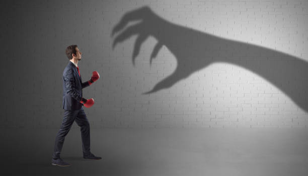 Businessman fighting with scary hand shadow stock photo