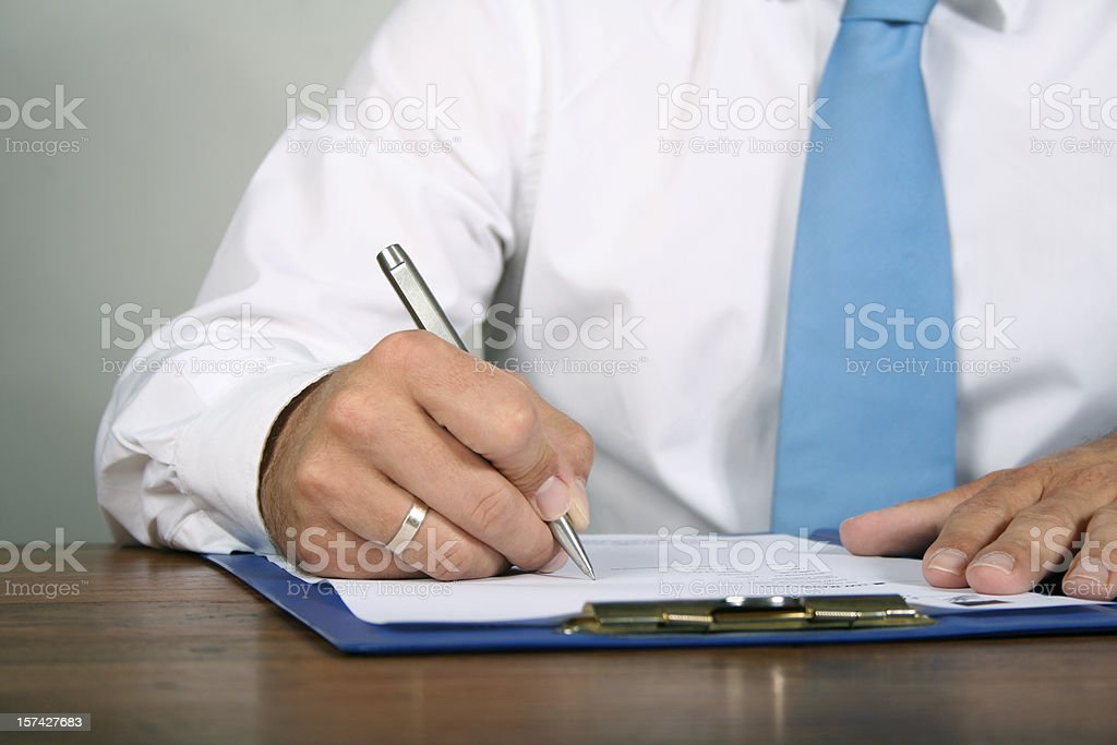 businessman fillin out papers stock photo