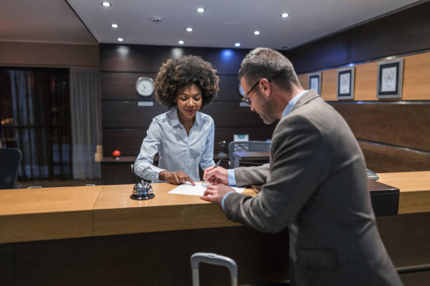 Businessman filling in the registration card at the hotel stock photo
