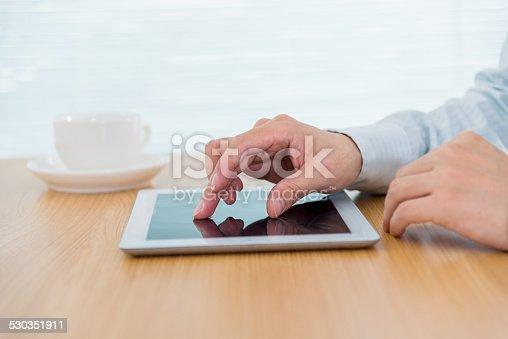 istock Businessman finger touching digital tablet 530351911