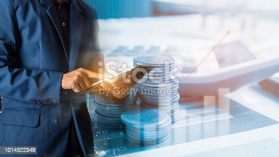 611747524istockphoto Businessman finger touching tablet with finance and banking profit graph of stock market trade indicator financial 1014522348