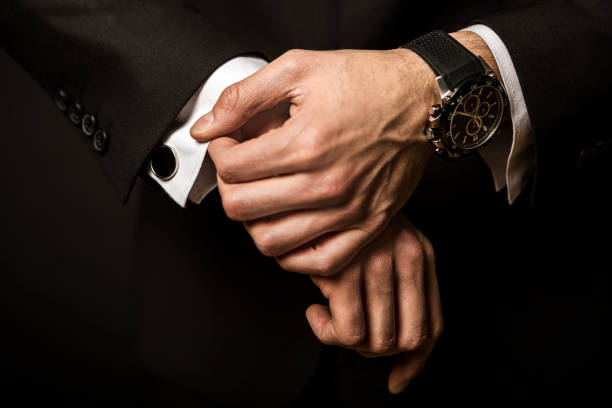 businessman fixing cuff links - watch timepiece stock photos and pictures