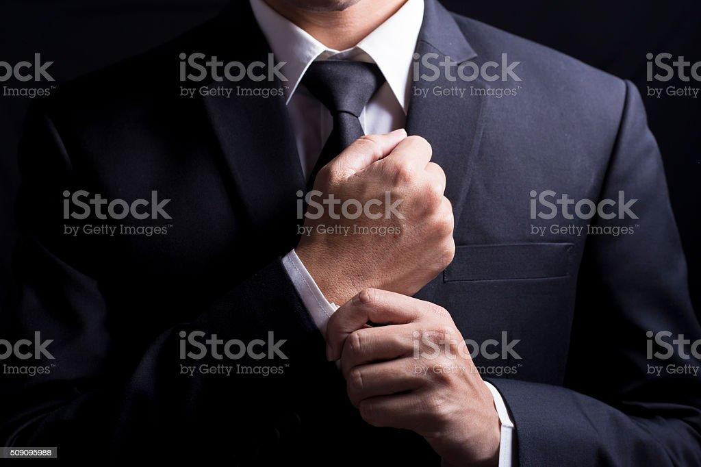 Businessman Fixing Cufflinks his Suit stock photo