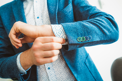 516141885 istock photo Businessman Fixing Cufflinks his Suit 696258874