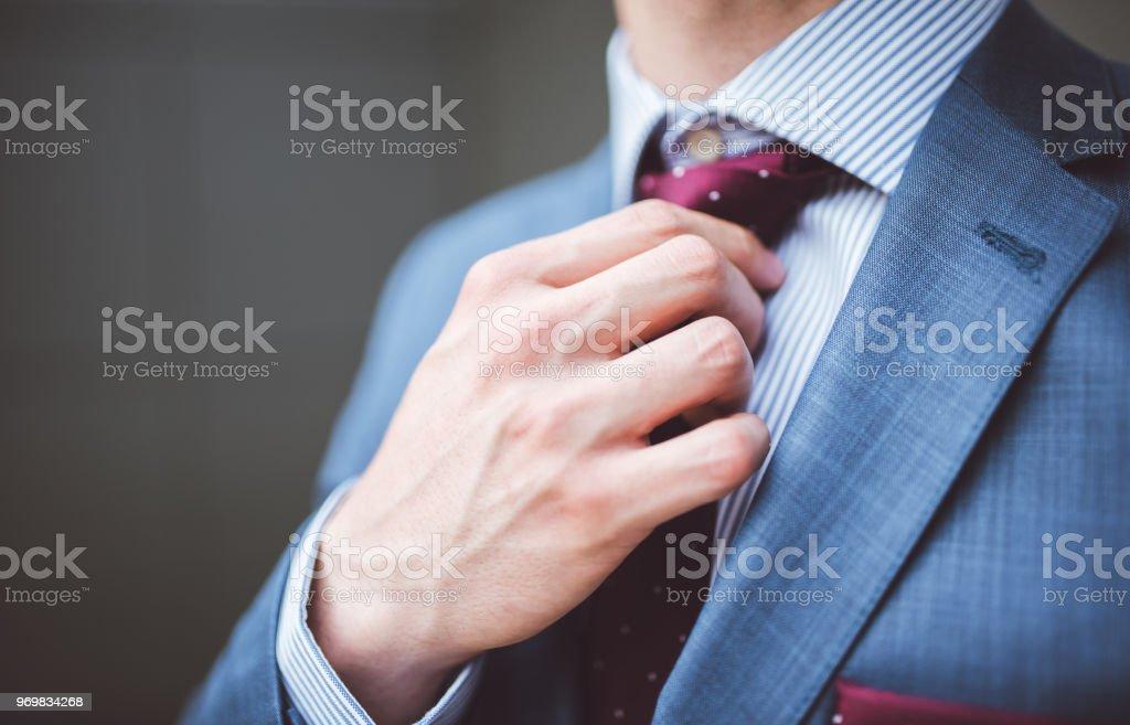 Businessman fixing his tie stock photo