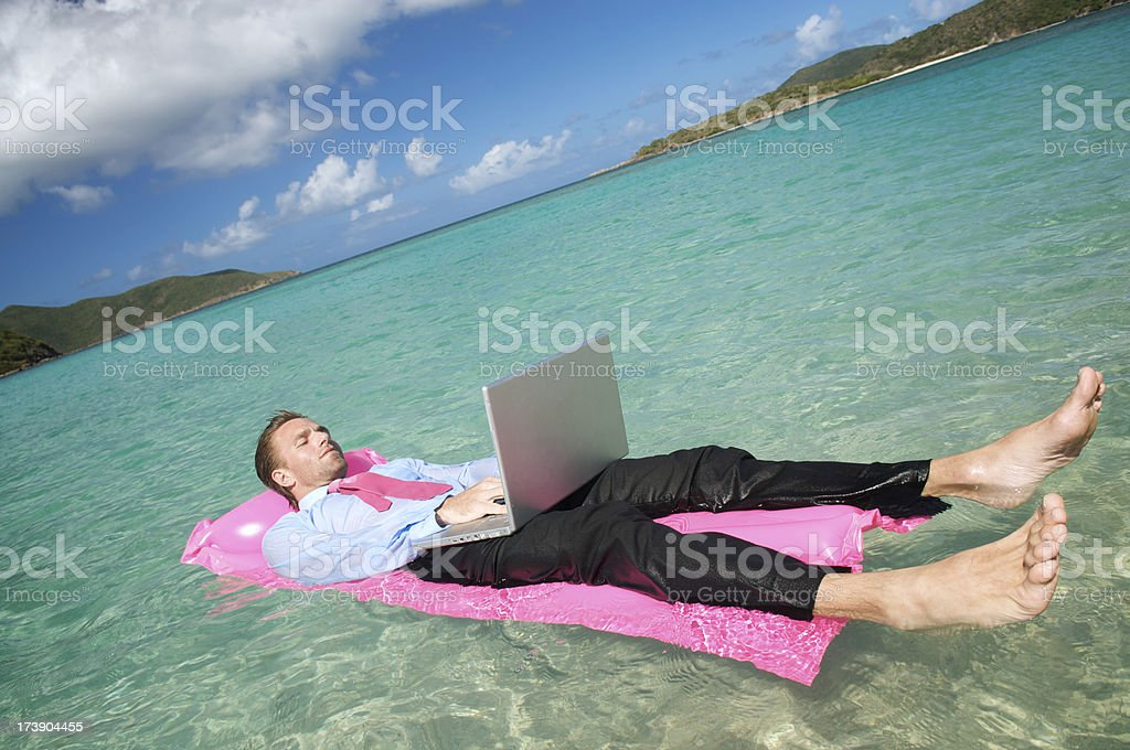 Businessman Floating on a Lilo Working Laptop royalty-free stock photo