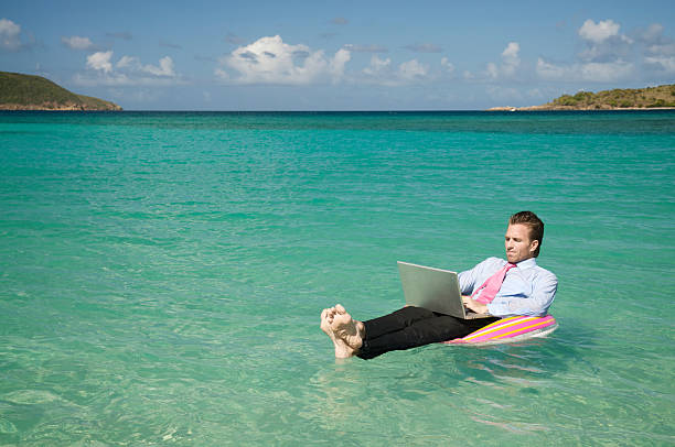 Businessman Floating Outdoors in Tropical Sea Working on Laptop stock photo