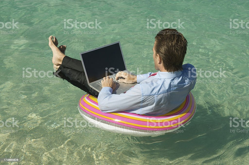 Businessman Floats and Works on Colorful Ring Tropical Sea royalty-free stock photo