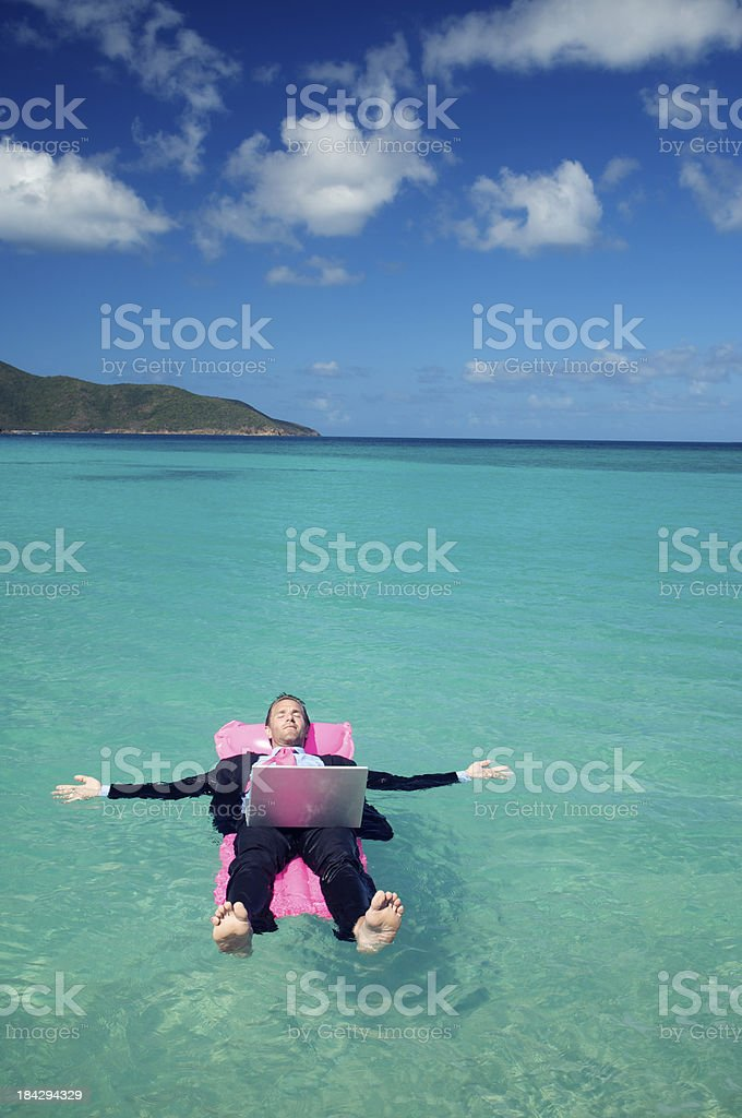 Businessman Floats in Tropical Bay with his Laptop royalty-free stock photo