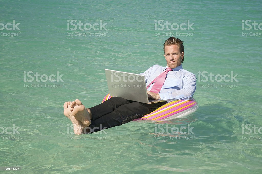 Businessman Floats with Laptop in Crystal Blue Waters stock photo