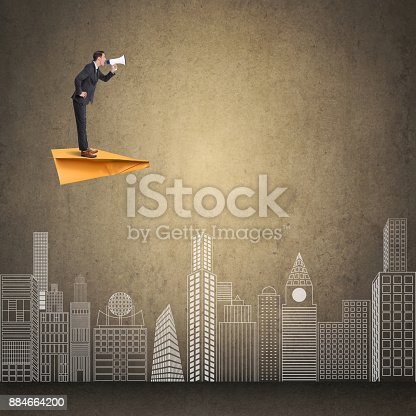 903659714istockphoto Businessman flying on paper airplane and speaking on megaphone 884664200