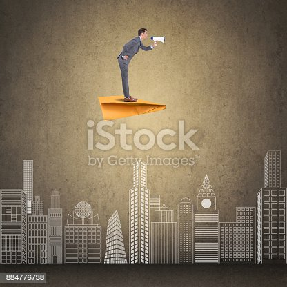 903659714istockphoto Businessman flying on paper airplane and speaking on megaphone 884776738
