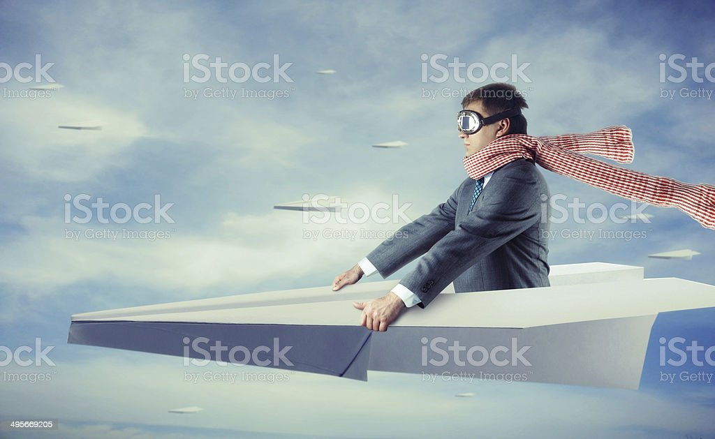 Businessman flying on paper plane stock photo