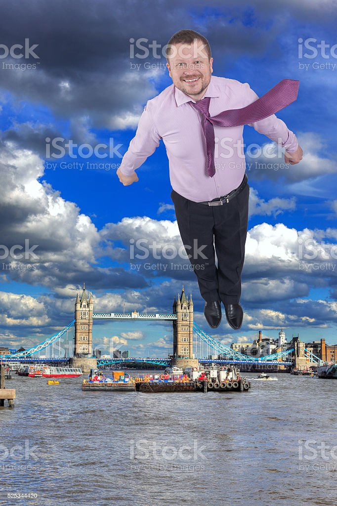 Businessman flying up with Tower bridge London UK in background stock photo