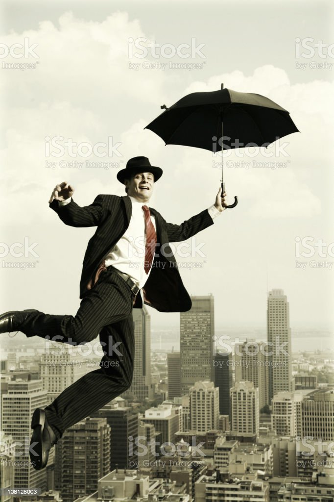 Businessman Flying with Umbrella Over City royalty-free stock photo