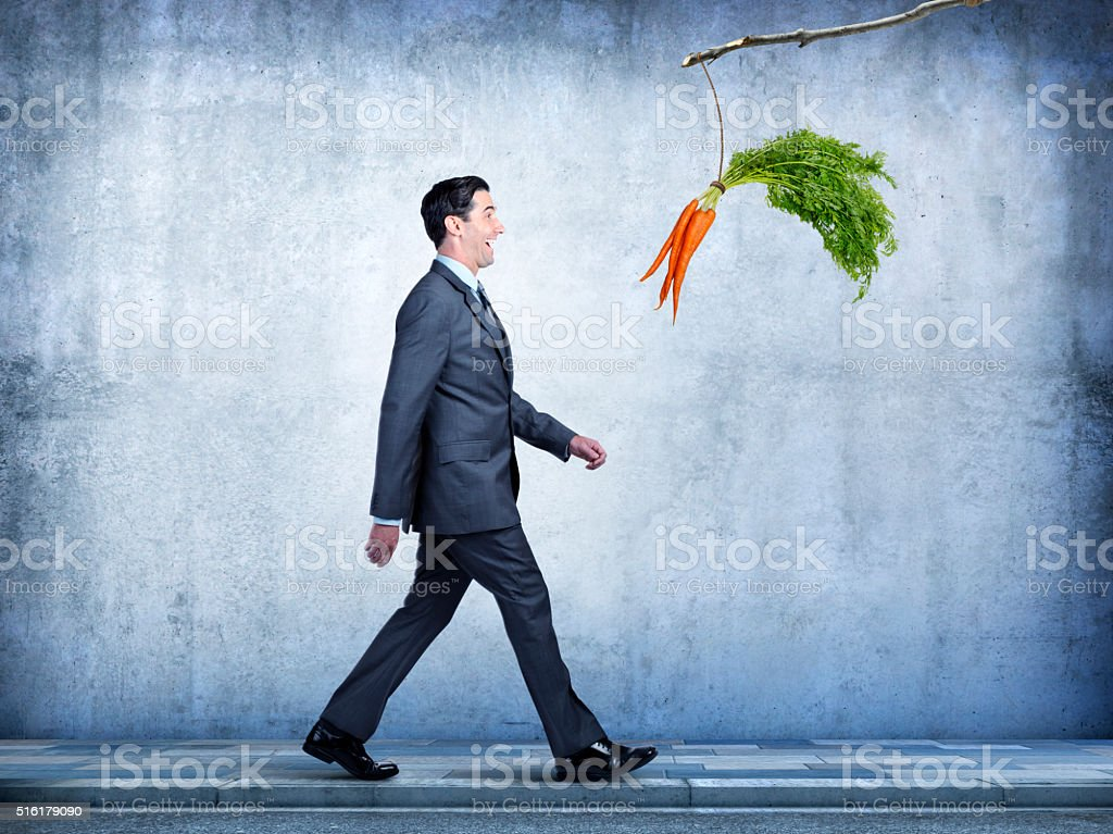 Businessman Follows Carrots Dangling From A Stick stock photo
