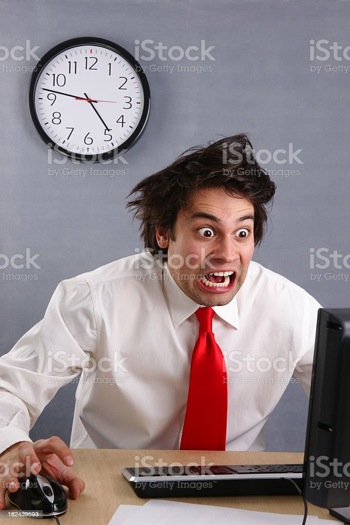 Businessman freaking out at computer in front of clock royalty-free stock photo