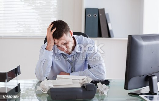690496350istockphoto Businessman frustrated by paperwork 826504854