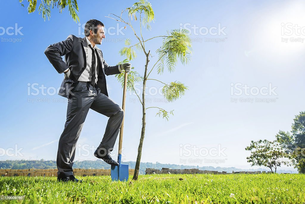 Businessman gardening against the sky. royalty-free stock photo