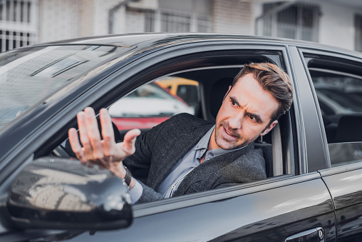 An attractive businessman is seen getting angry in the car.
