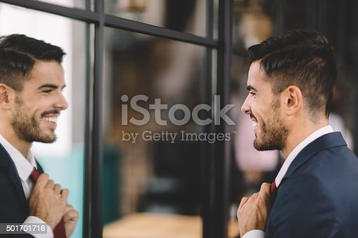 istock Businessman getting dressed in front of the mirror 501701716