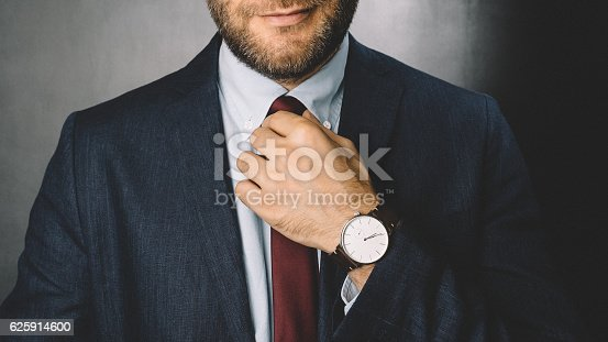 Smiling businessman fixing his necktie before going to work