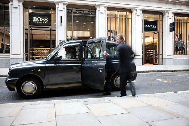 Businessman getting into taxi cab in front of fashion store stock photo