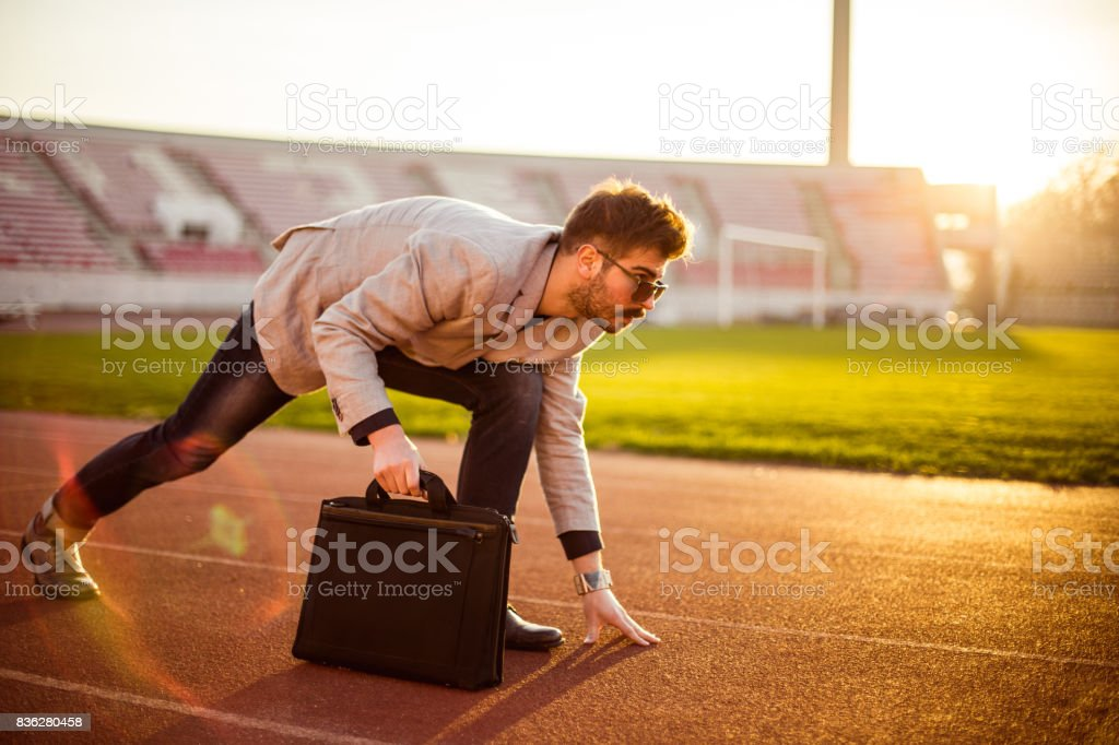 Businessman getting ready for career race stock photo