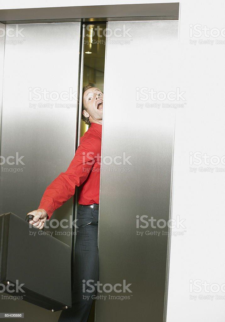 Businessman getting stuck in elevators doors stock photo