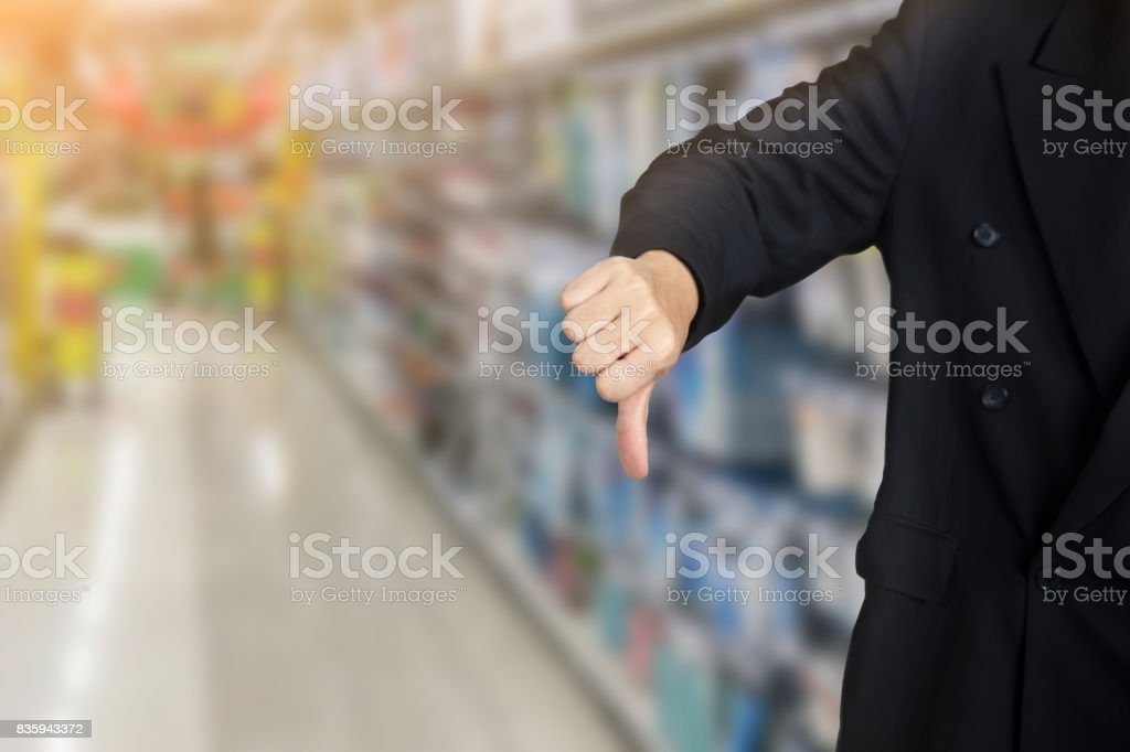 businessman give bad thumbs down on supermarket background stock photo