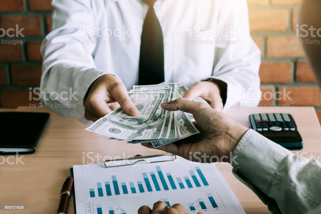 Businessman give dollar bills to partner. stock photo