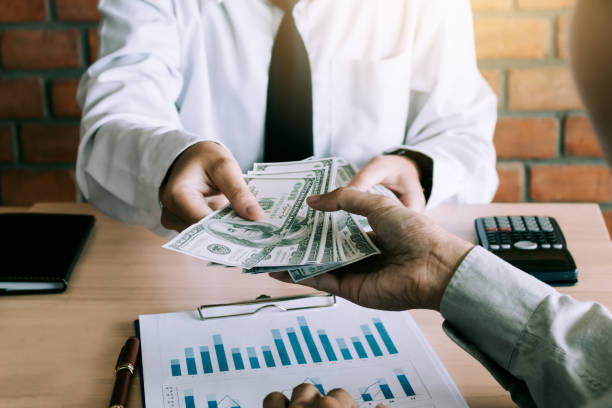businessman give dollar bills to partner. - spending money stock pictures, royalty-free photos & images