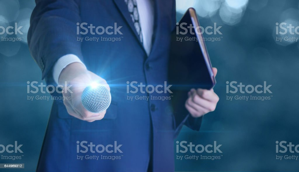 Businessman gives a microphone. stock photo